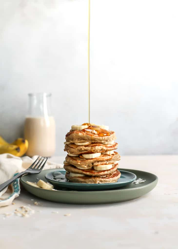syrup pouring onto stack of oatmeal banana pancakes
