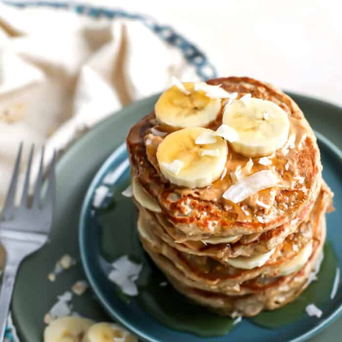 stack of pancakes with banana slices and flaked coconut