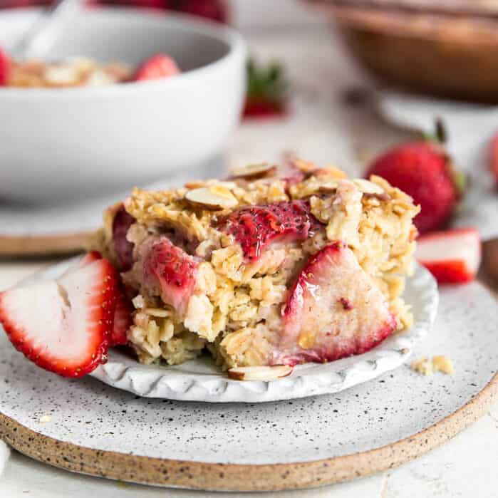 piece of strawberry baked oatmeal on plate next to fresh cut strawberry