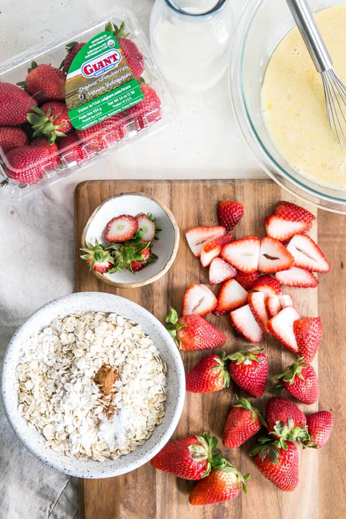 sliced strawberries on board next to bowl of oats