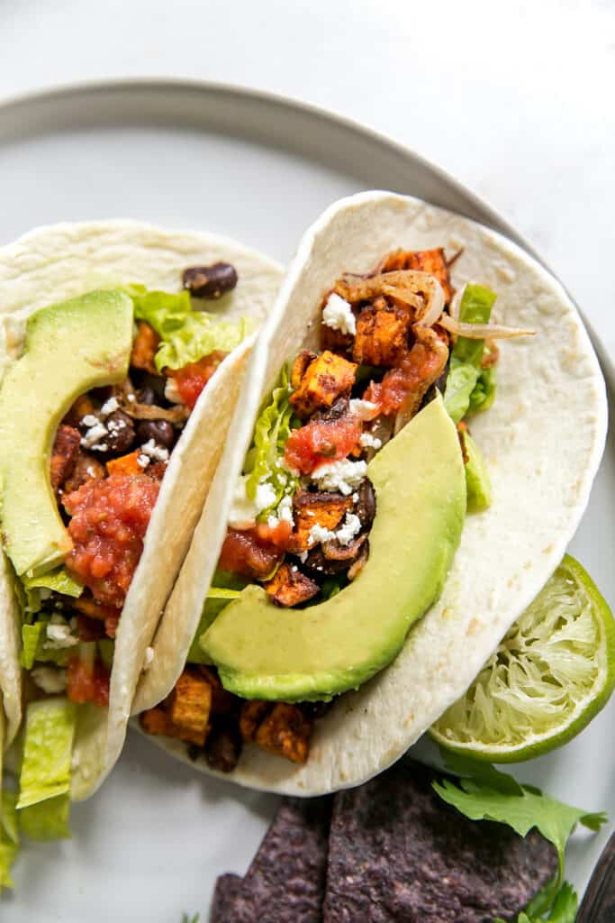 plate of tacos topped with sweet potatoes, black beans, salad, avocado, and lime.