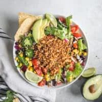 vegan burrito bowl with striped towel and avocado half