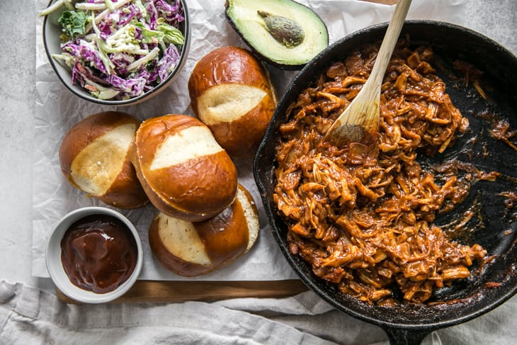 skillet, pretzel buns, coleslaw, bbq, and avocado on a wooden cutting board