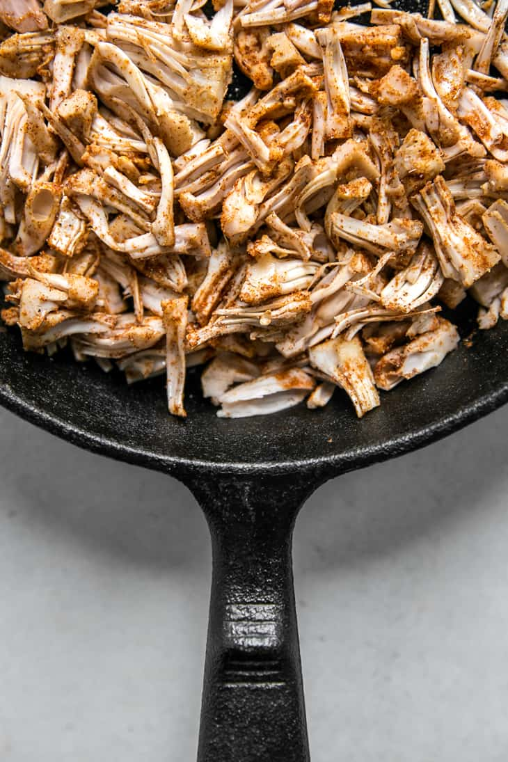 shredded jackfruit topped with spices in a skillet