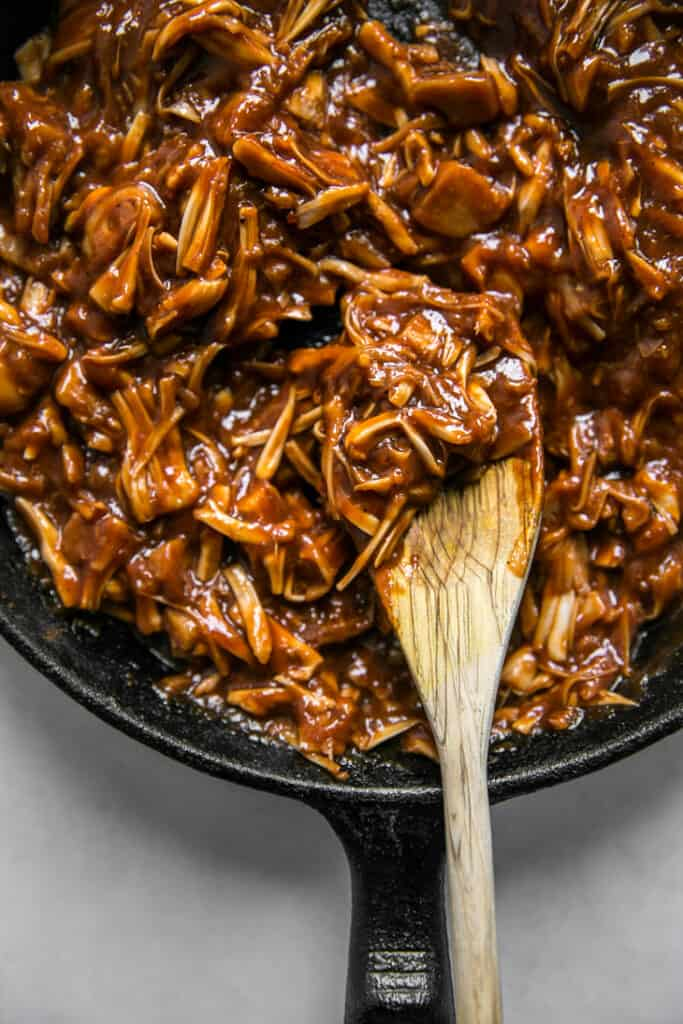bbq jackfruit in a skillet with a wooden spoon