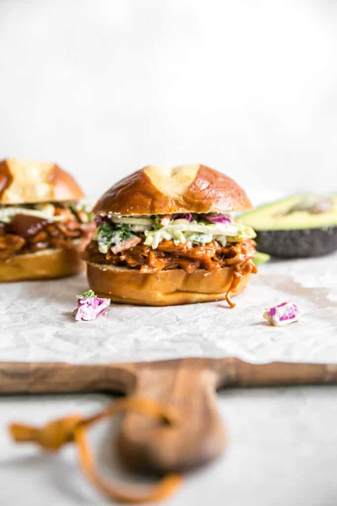 bbq pulled pork on a wooden board with avocado