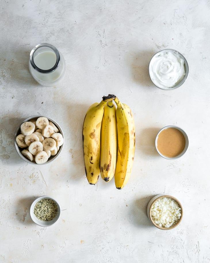 banana, sliced bananas, yogurt, peanut butter, cauliflower, hemp hearts and milk in bowls on white board