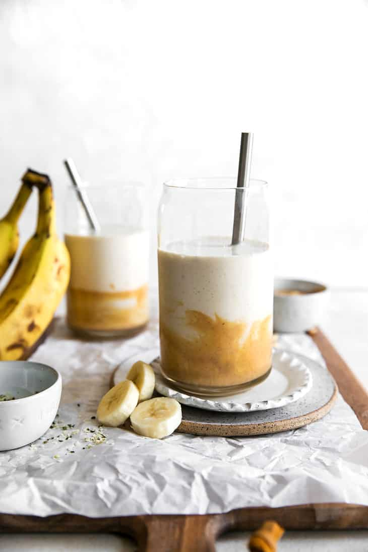 peanut butter banana smoothie in glasses with metal straw