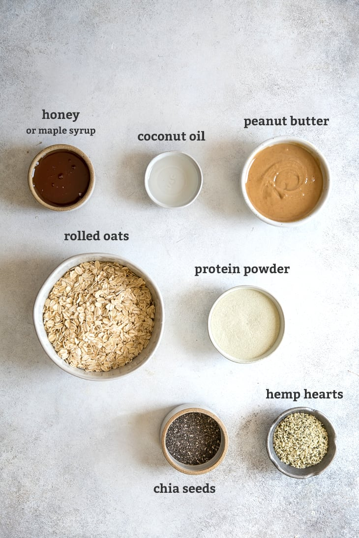 honey, coconut oil, peanut butter, rolled oats, protein powder, chia seeds and hemp hearts in bowls, with text by bowls