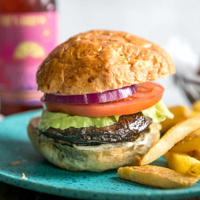 mushroom burger with lettuce, tomato and red onion, on turquoise plate with pink beer bottle in backgroun