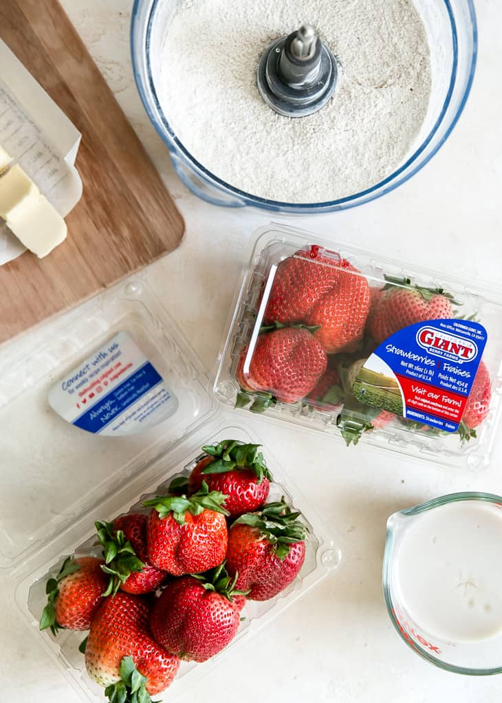 two containers of california giant strawberries on white board, next to glass measuring cup of milk, food processor bowl of flour, and stick of butter on wooden board