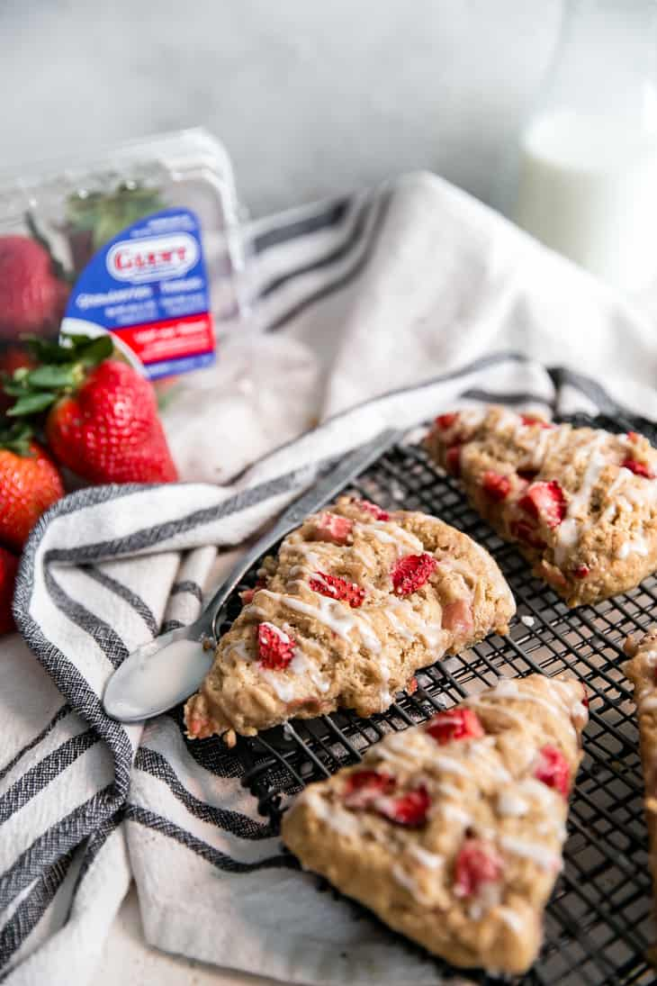 glazed strawberry scone on black wire cooling rack, next to spoon with glaze, carton of California Giant Strawberries in background