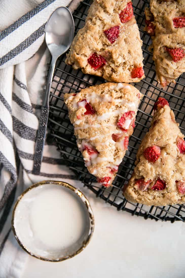 strawberry scones on black cooling rack with glaze over top, silver spoon and bowl of glaze