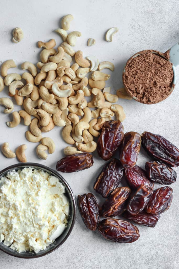 cashews, medjool dates, cocoa powder in measuring cup and egg white protein powder in bowl