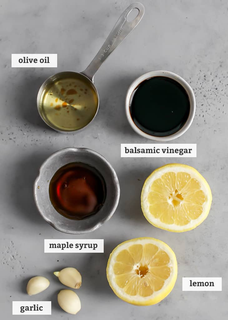 olive oil, balsamic vinegar, lemons, maple syrup and garlic on gray board, with text labels