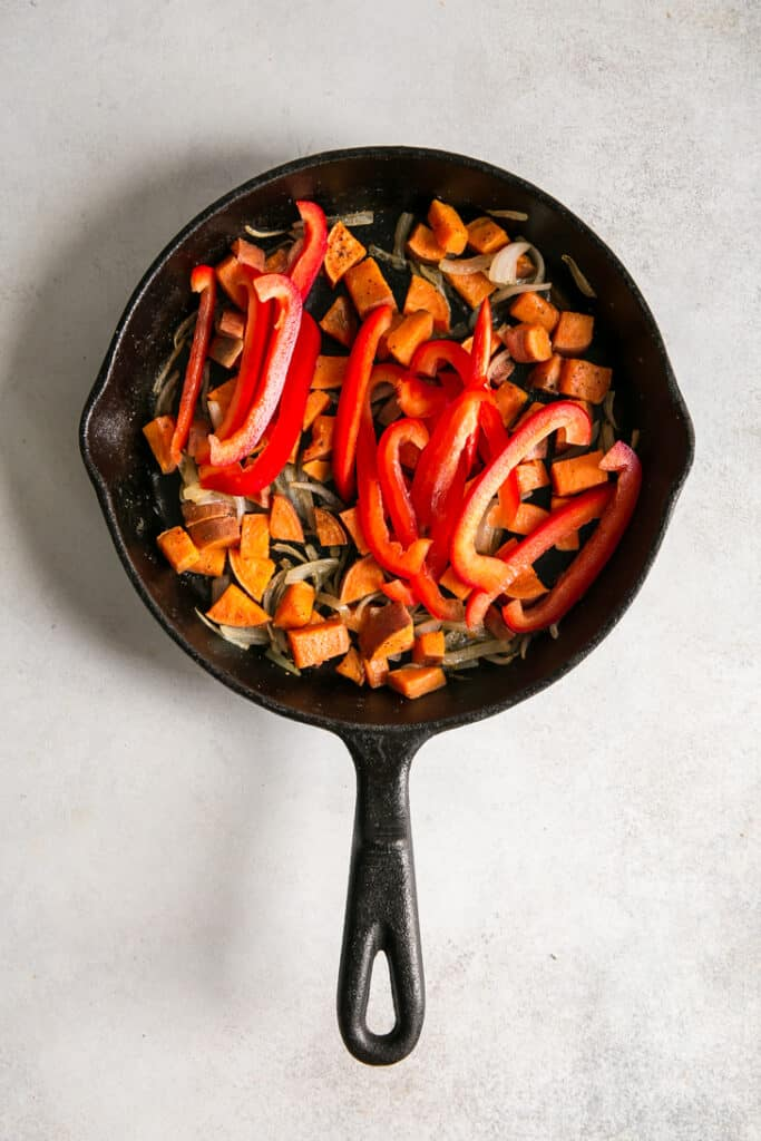 red bell pepper, chopped sweet potatoes, and onion in cast iron skillet