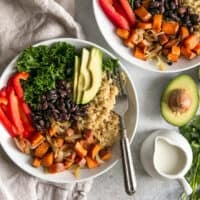 two power bowls with sweet potatoes, red bell pepper, avocado, quinoa and kale next to dressing pitcher and avocado half