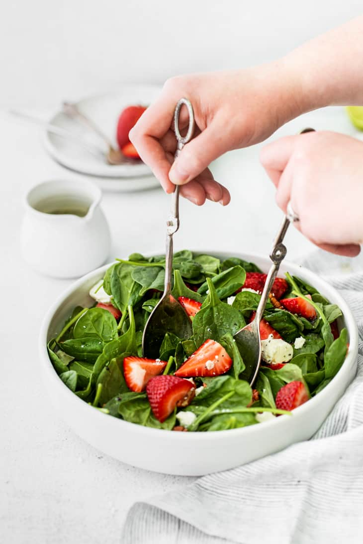 hands using silver salad tongs in bowl of spinach with strawberries