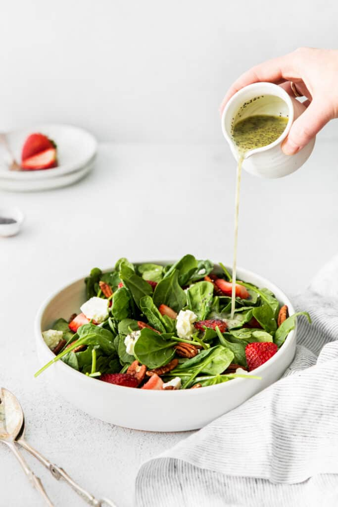 poppy seed dressing pouring into bowl of spinach salad with feta and strawberries on top