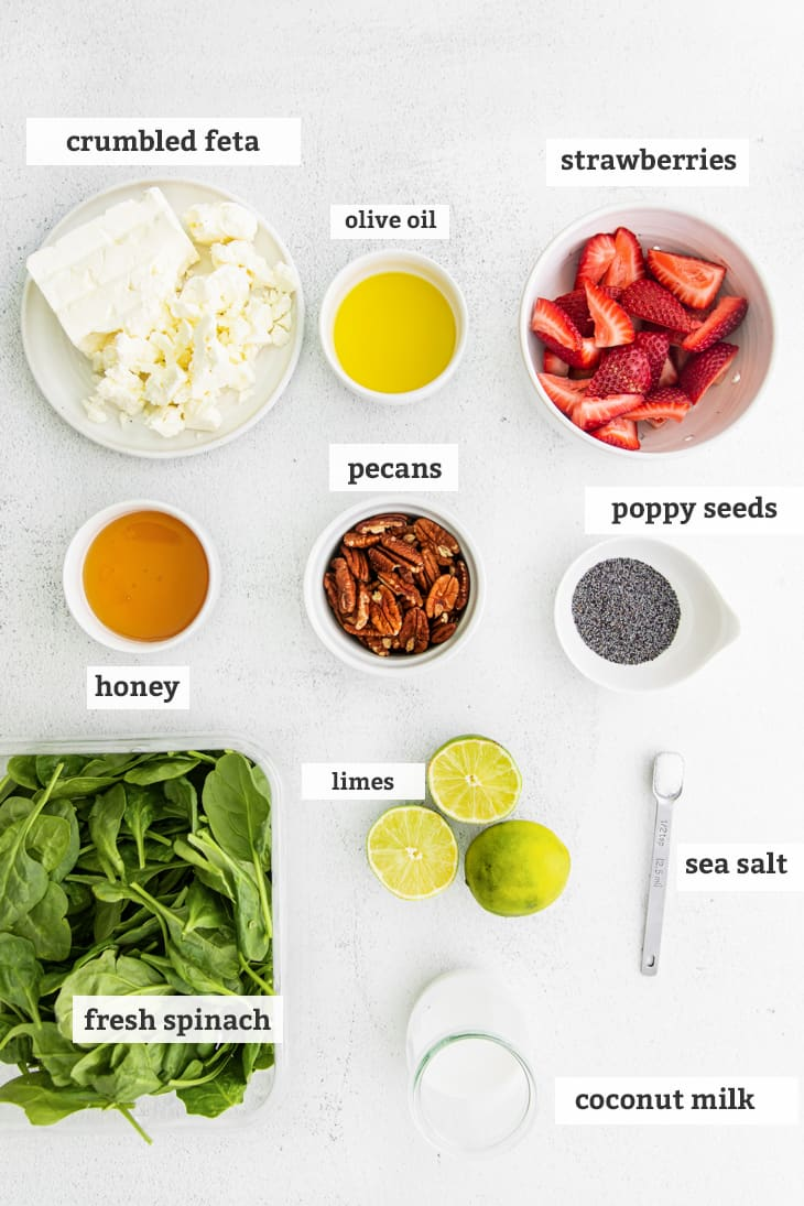 ingredients on board, labeled, crumbled feta, olive oil, strawberries, honey, pecans, poppy seeds, limes, fresh spinach, sea salt and coconut milk