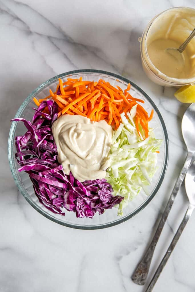 dressing in glass bowl on top of shredded cabbage and carrots for vegan coleslaw