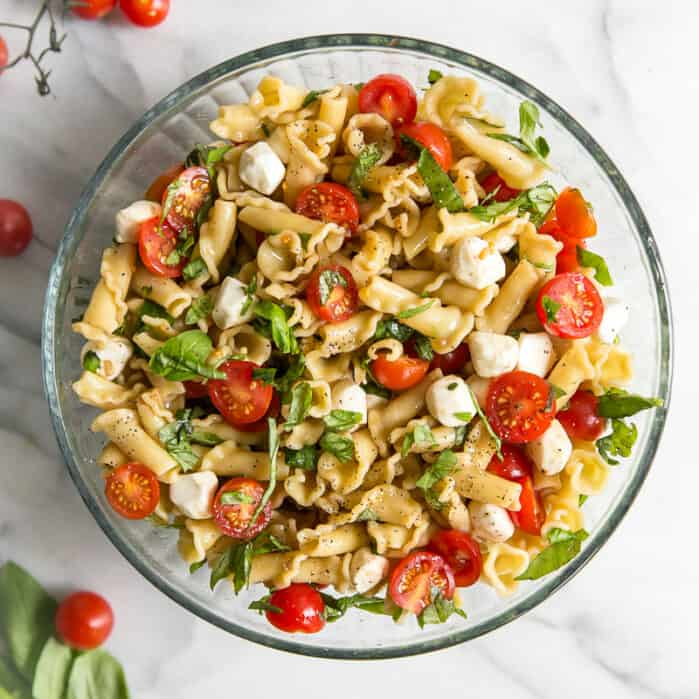 pasta, tomatoes, basil and mozzarella pears in glass bowl on marble board