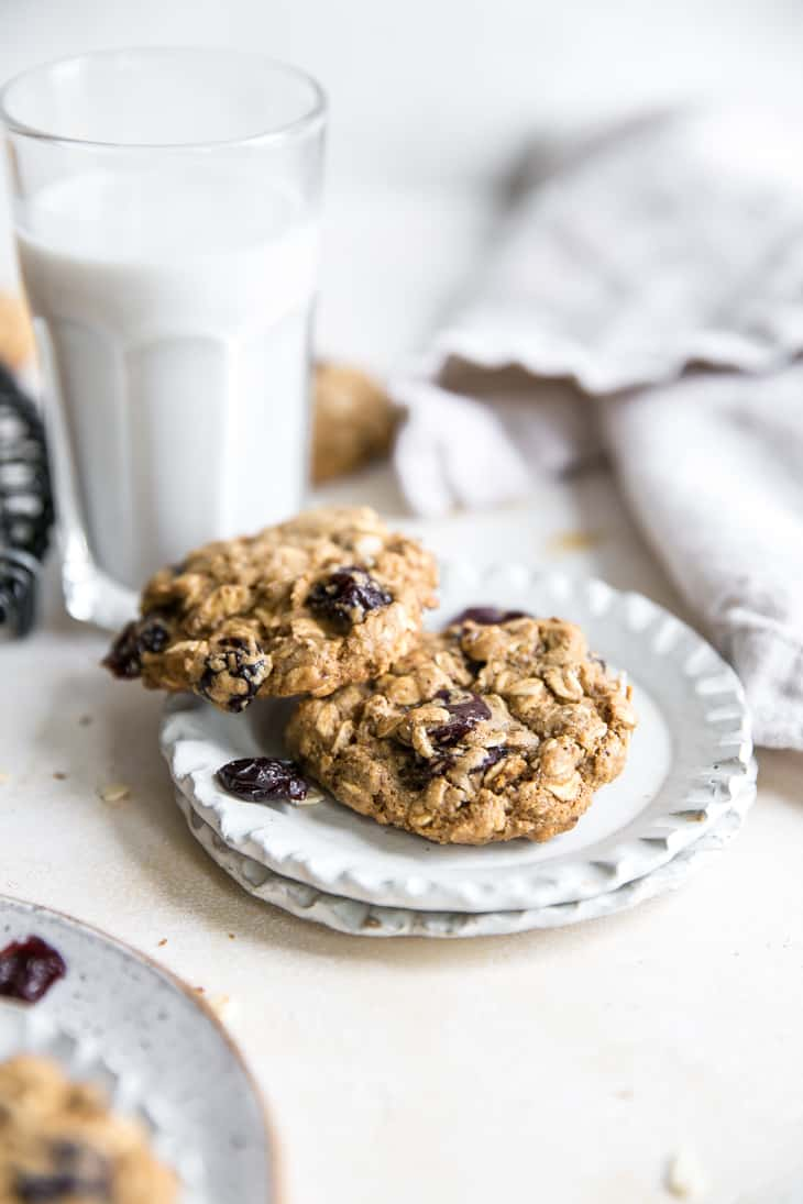 cherry oatmeal cookies on a plate with glass of milk behind