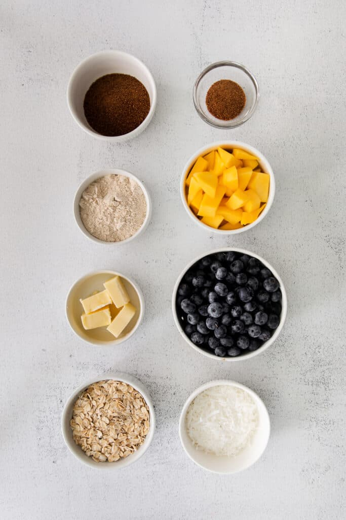 ingredients for blueberry crisp in bowls on board