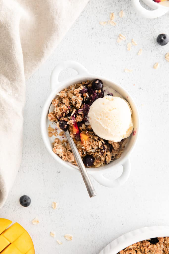 mango blueberry crisp in small serving bowl with ice cream scoop