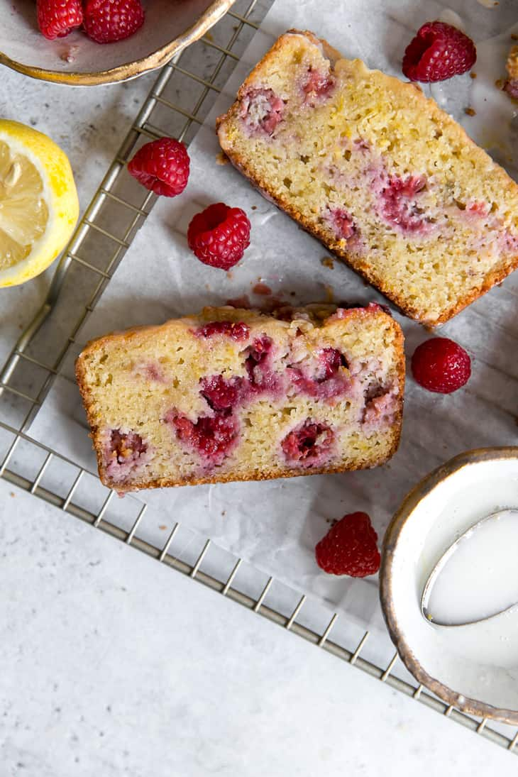 lemon raspberry bread slice on cooling rack next to raspberries and lemon