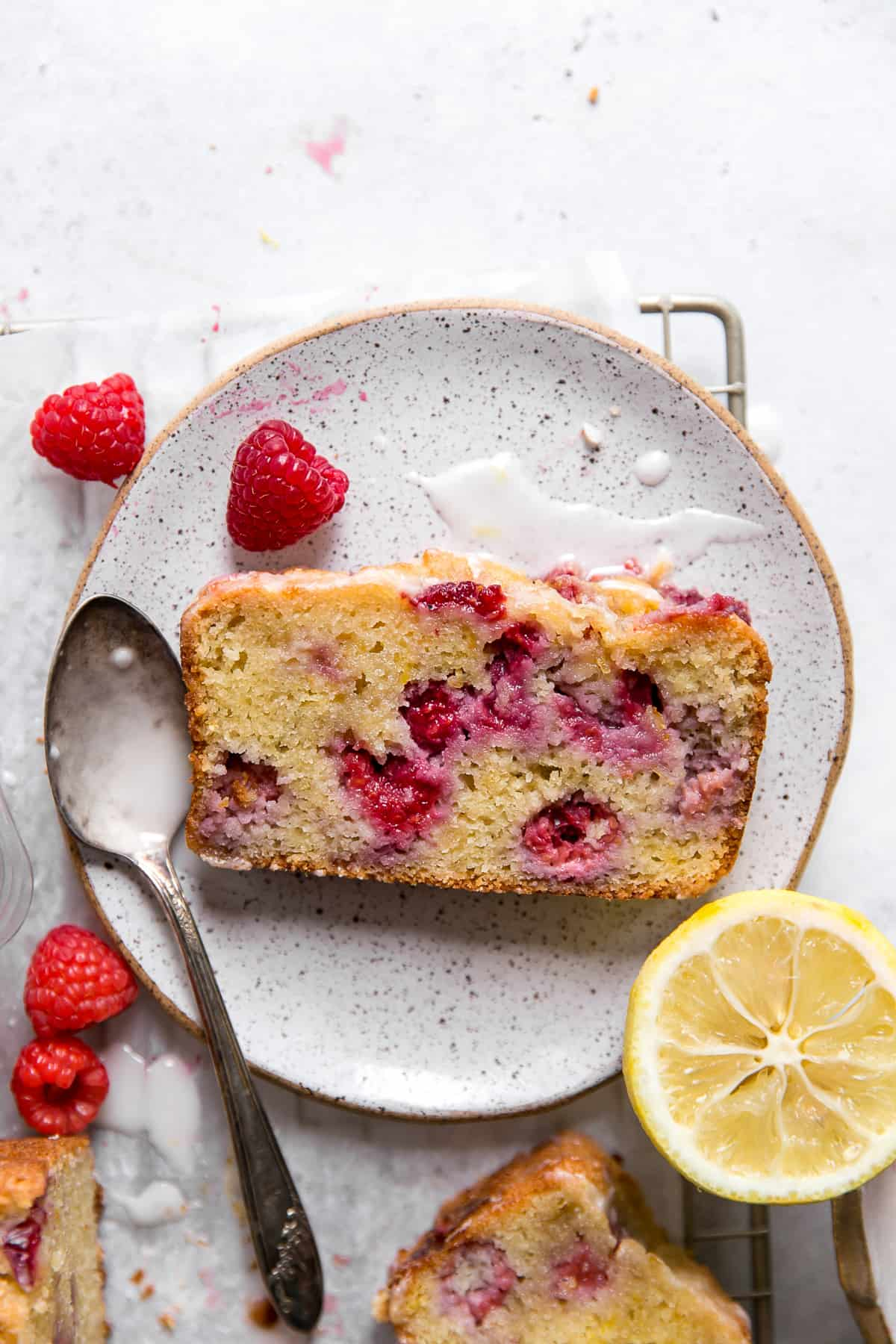raspberry lemon loaf on plate next to spoon with glaze and lemon round