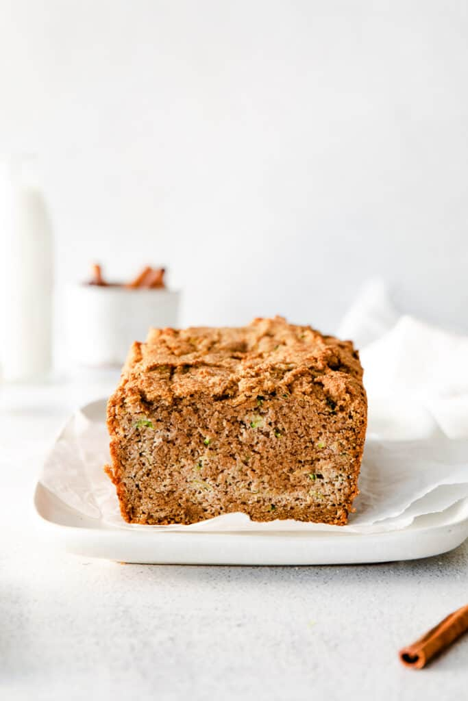 almond flour zucchini bread on white serving diwh with milk and cinnamon in background
