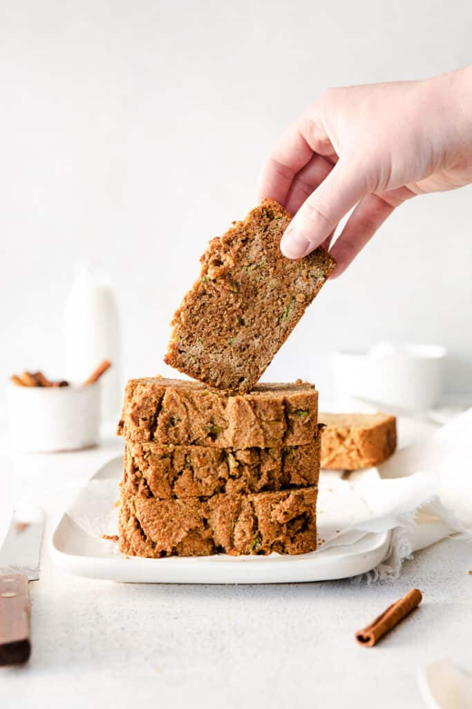 hand holding zucchini bread over stack