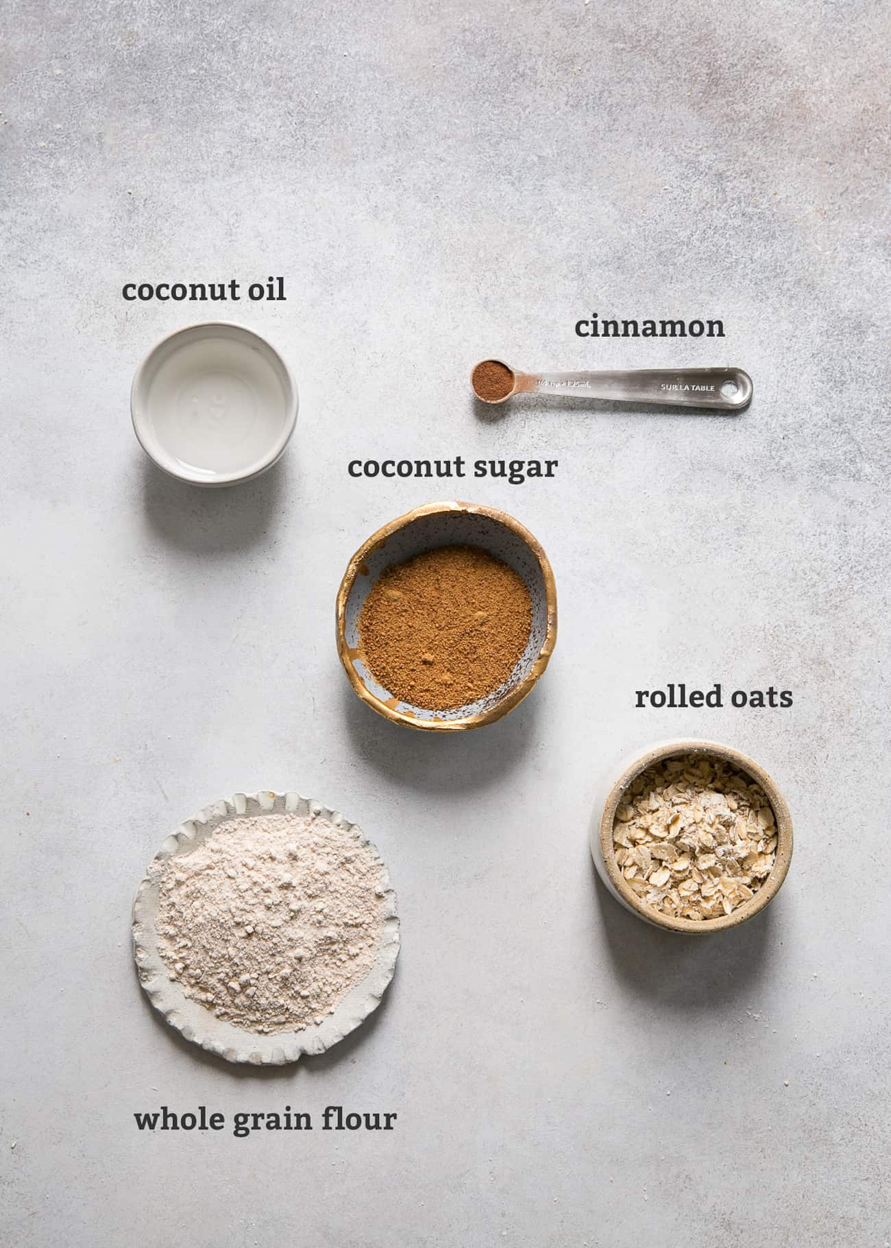 ingredients in bowls and spoons on board; text labeled: coconut oil, cinnamon, coconut sugar, rolled oats, whole grain flour