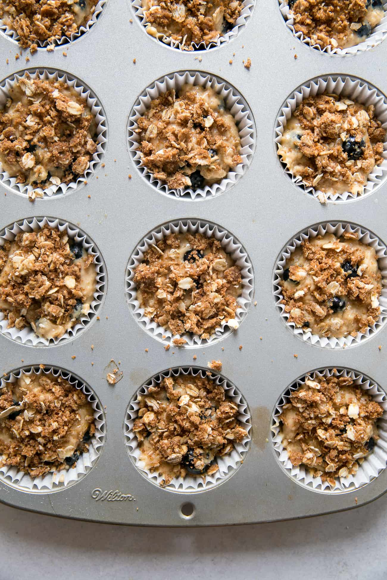 blueberry muffin batter with crumble sprinkled in each muffin cup