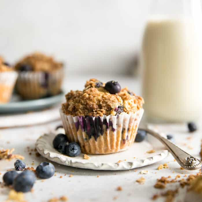 blueberry muffin with oat crumble on top, in liner on small white plate, muffins on plate and glass of milk in background
