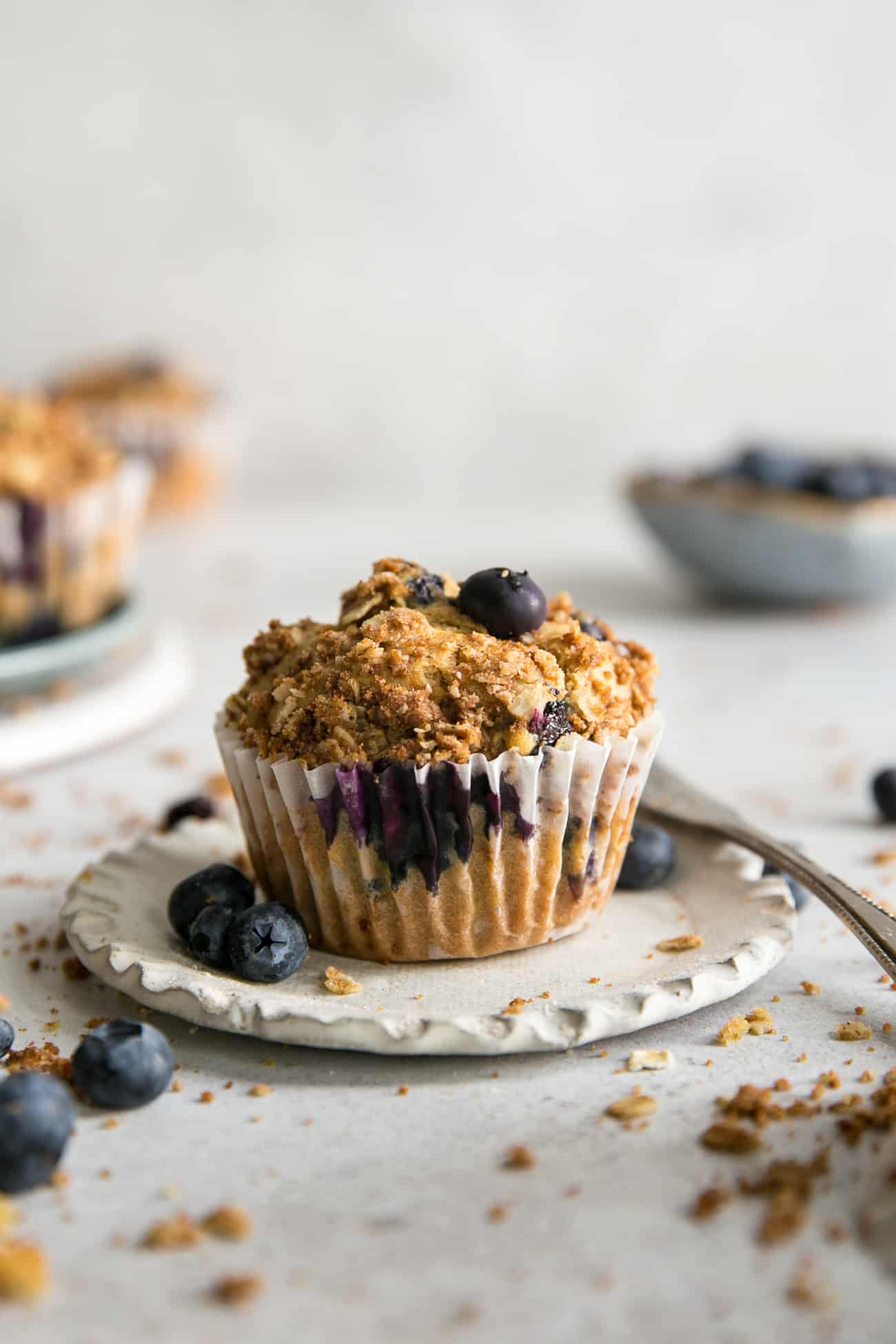 blueberry muffin with oat crumble on top, in liner on small white plate, blueberry bowl in background