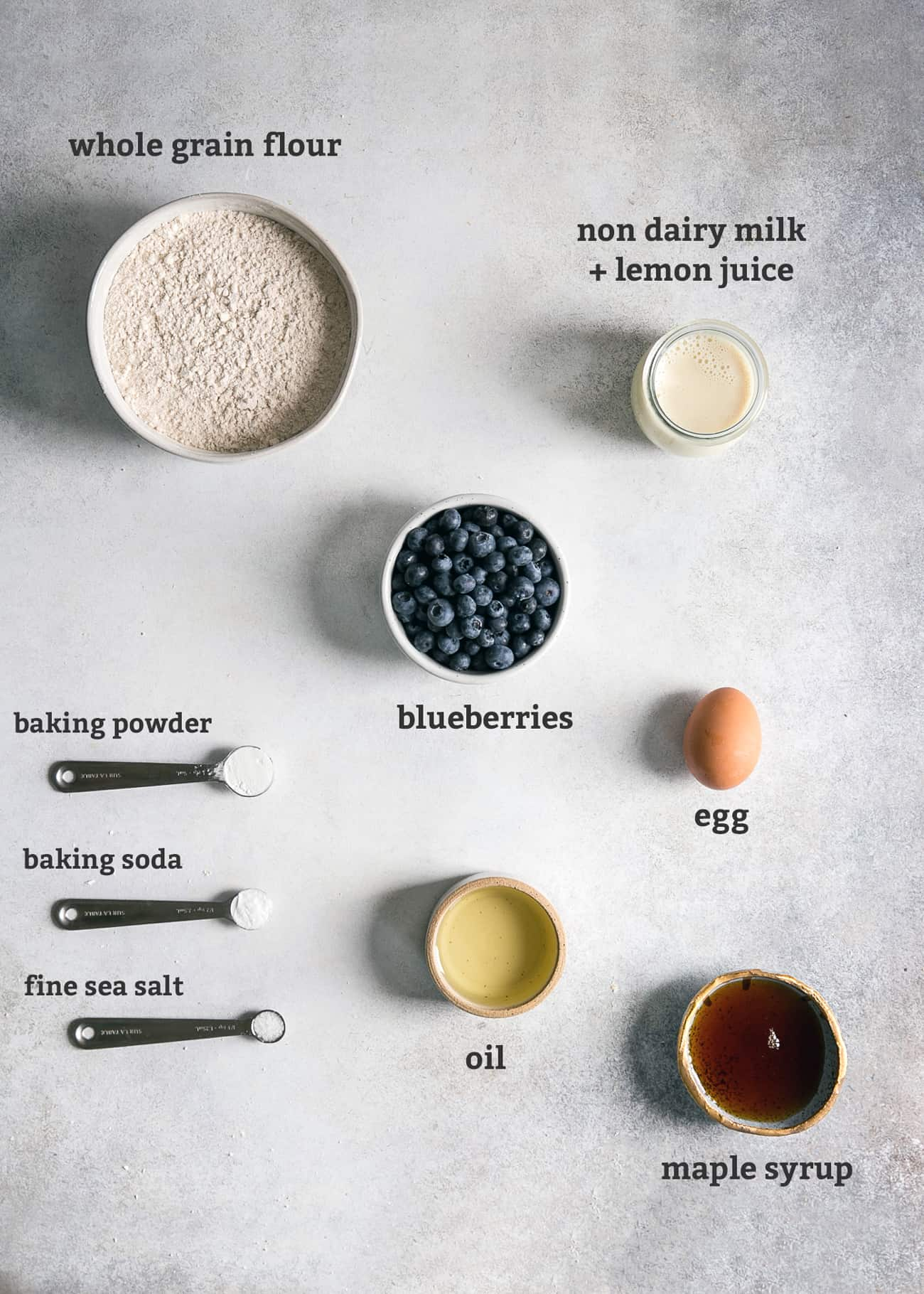 ingredients in bowls and spoons on board; text labeled: whole grain flour, non dairy milk + lemon juice, blueberries, egg, oil, maple syrup, fine sea salt, baking soda, baking powder