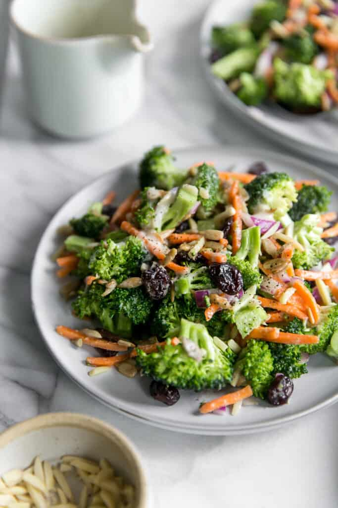 healthy broccoli salad on gray plate with dressing cup in background