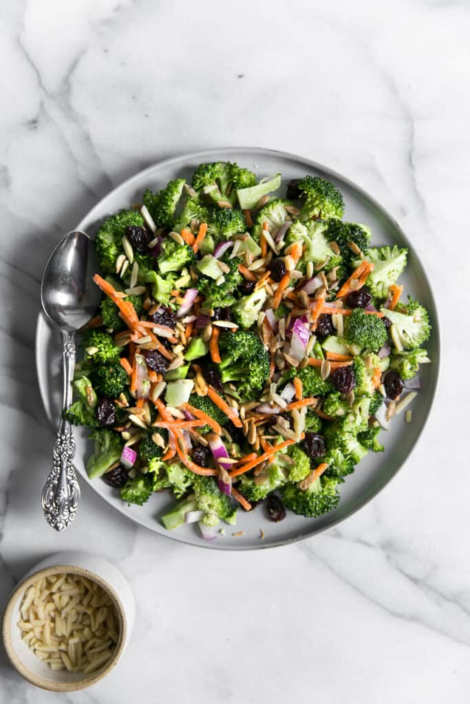 broccoli salad with onions, carrots, cherries, almonds, and sunflower seeds on gray plate with silver spoon on marble board