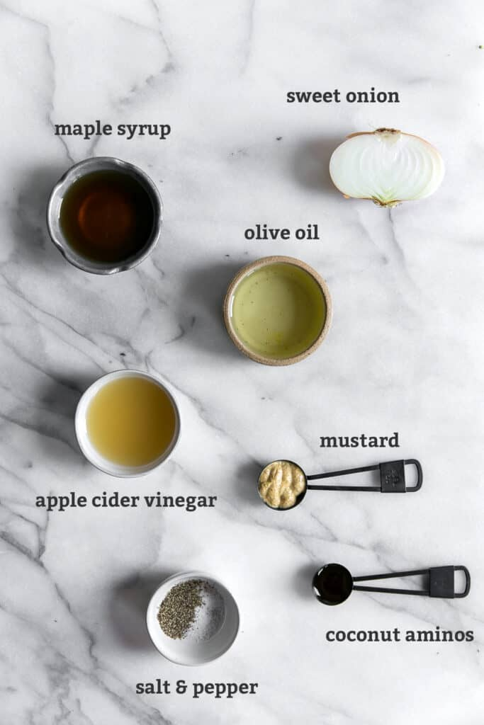 ingredients in bowls with text above; maple syrup, sweet onion, olive oil, apple cider vinegar, mustard, coconut aminos, salt & pepper