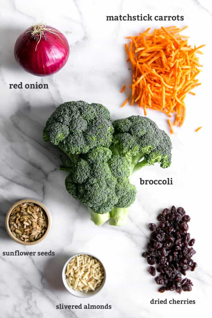 red onion, carrots, broccoli, sunflower seeds, almonds and dried cherries on marble board, text labeled next to each ingredient
