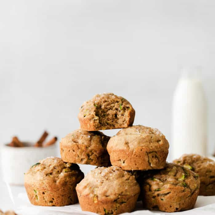 stacked zucchini muffins on wooden board with milk and cinnamon sticks in background