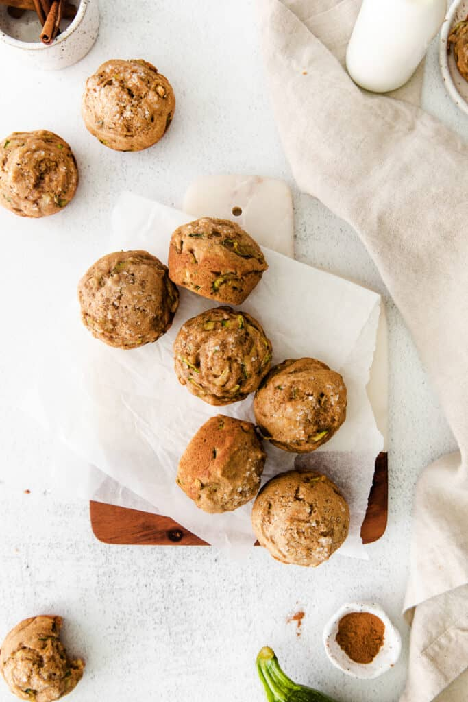 zucchini muffins on parchment paper on small board next to napkin