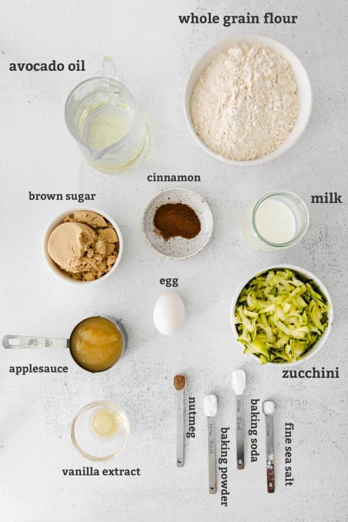 avocado oil, whole grain flour, brown sugar, cinnamon, milk, egg, applesauce, vanilla extract, nutmeg, baking powder, soda and salt, and zucchini on white board