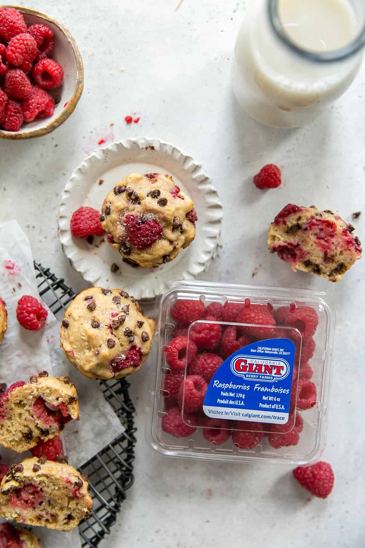 plate with raspberry chocolate chip muffins, glass of milk, bowl of raspberries and container of raspberries on white board
