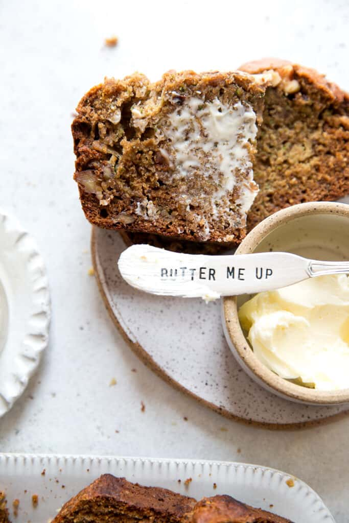 """knife over butter dish with engraving """"butter me up"""", with slice of banana zucchini bread covered in butter"""