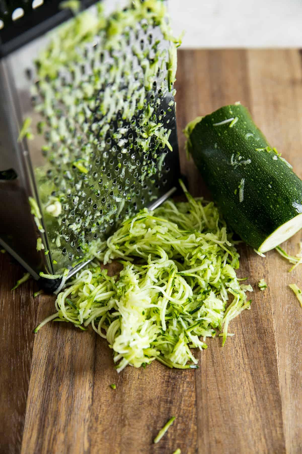 shredded zucchini next to box grater and cut zucchini