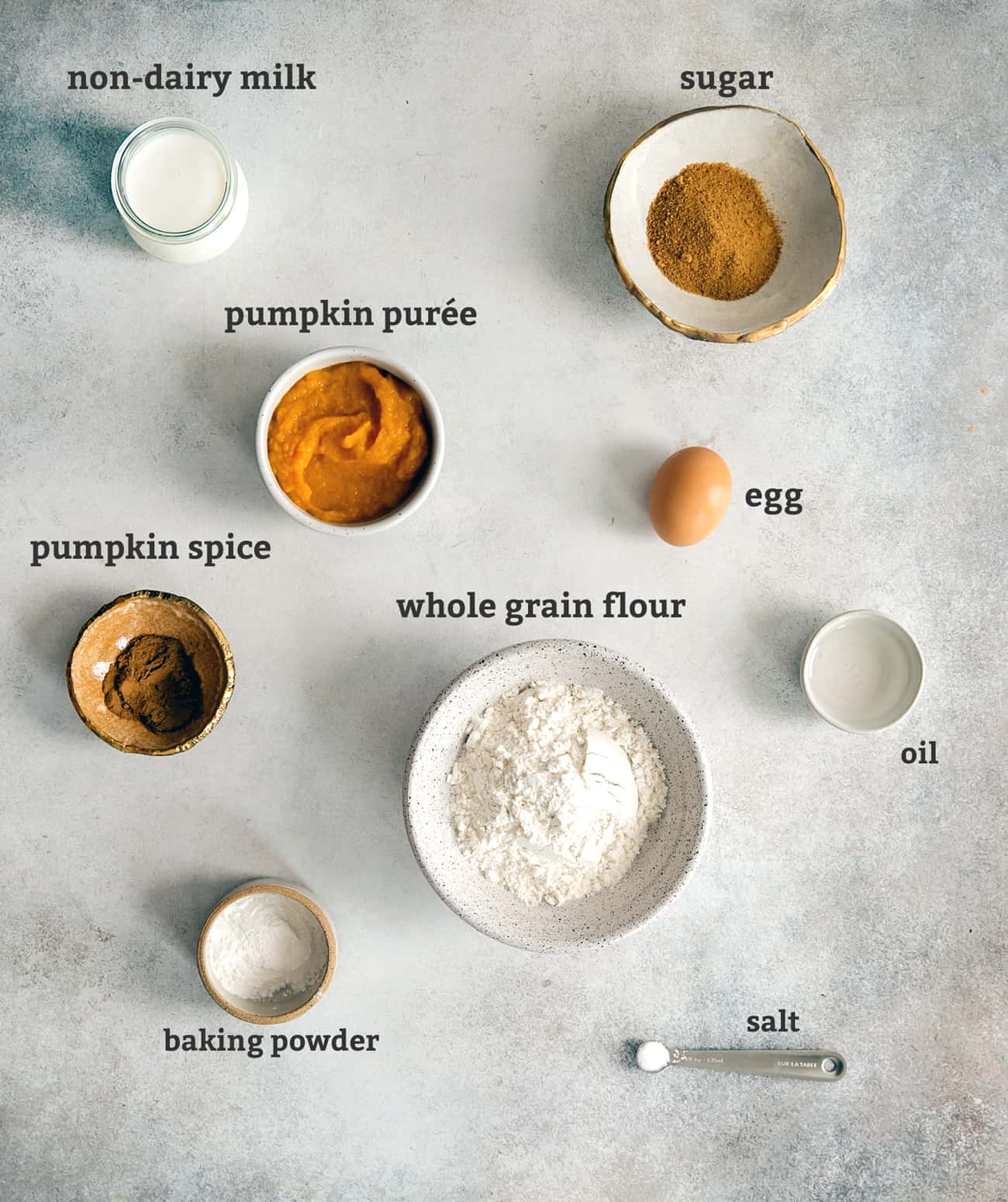 ingredients on board for pumpkin pancakes, in bowls and with text labels