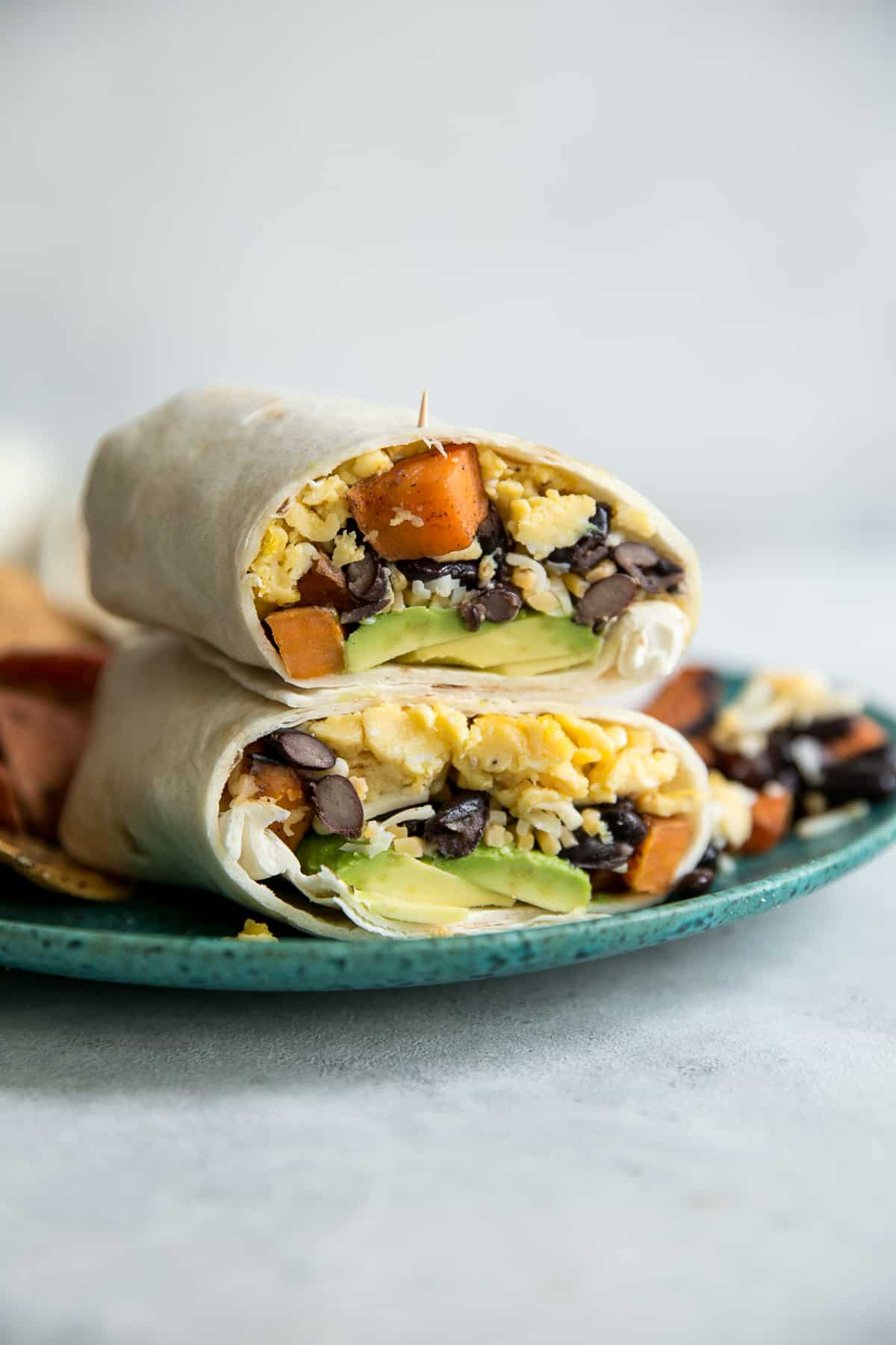 breakfast burrito on a teal plate with eggs sweet potatoes black beans and avocados